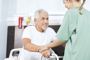 caregiver assisting patient to stand